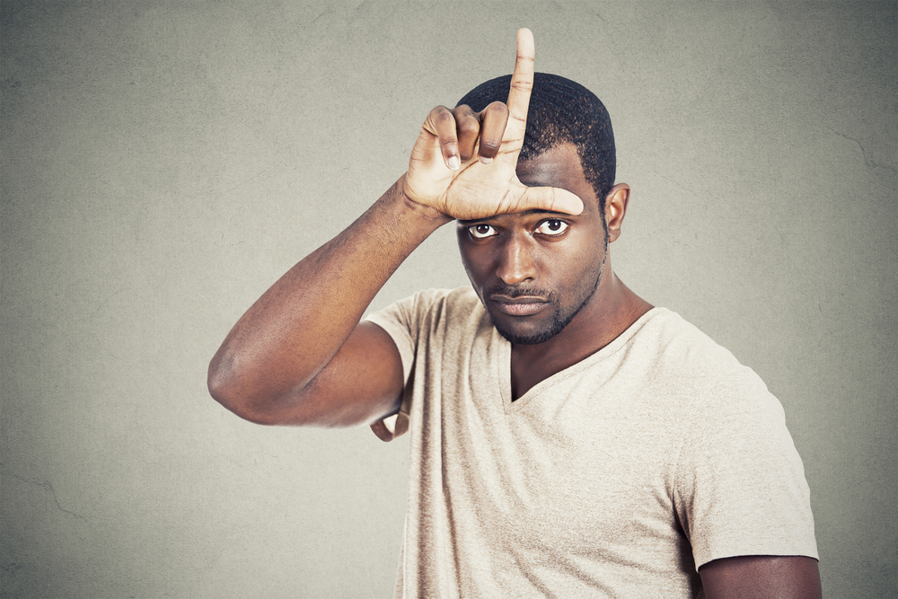Closeup portrait serious young man showing loser sign on forehead looking at you with disgust at camera isolated grey wall background. Negative human emotion facial expression feeling